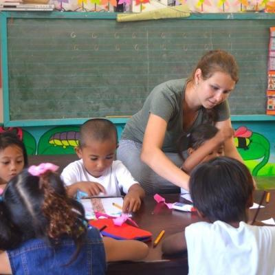 A Projects Abroad volunteer working with children in the Philippines teaches colouring exercises.